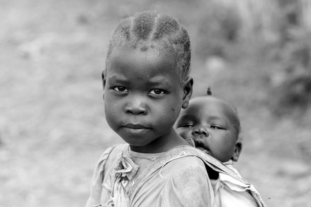 TORIT, SOUTH SUDAN-FEBRUARY 21 2013: An unidentified little girl in charge of carrying her baby sister in Torit, South Sudan