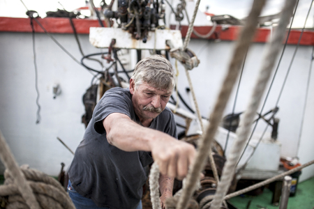 Deckhand doing hard work on a fishing vessel