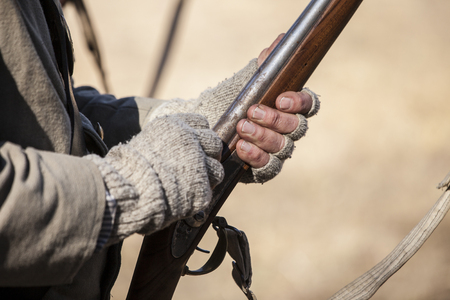 vintage rifle: Hands of man in vintage clothing holding muzzle loading rifle