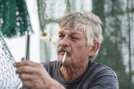 shrimp boat: weathered fisherman mends nets on a fishing boat Stock Photo