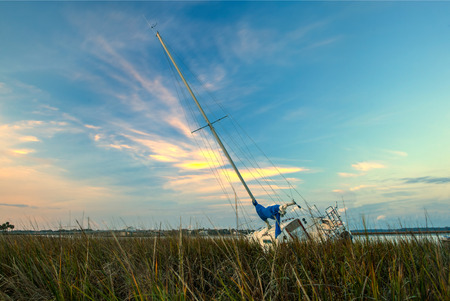 ship wreck: beached sailboat stuck in the marsh at sunset Stock Photo