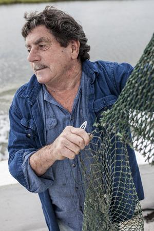 redes de pesca: pescador resistido arreglando redes en la cubierta de un barco