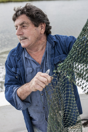 Weathered fisherman mending nets on the deck of a boat