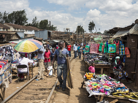 NAIROBI, KENYA-NOVEMBER 7, 2015: Unidentified people buy and sell in a large makeshift market along the railroad in Kibera, the largest urban slum in Africa. Редакционное