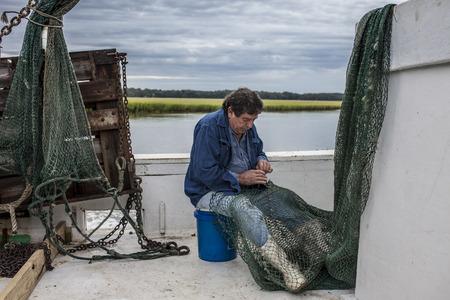 pecheur: pêcheur commercial raccommode ses filets sur le pont d'un bateau