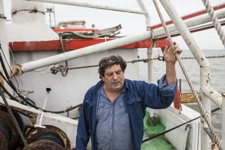 pescador: Comercial capitán de barco de pesca en la cubierta de su barco Foto de archivo