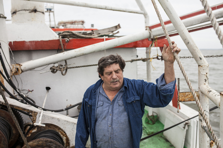 commercial fishing: Commercial fishing boat captain on deck on his ship Stock Photo