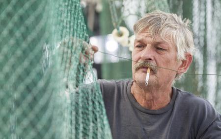 fisherman: Deckhand on commercial fishing vessel mending nets Stock Photo