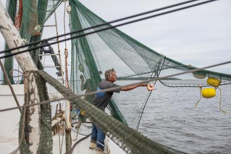 tending: commercial fishermen tending nets on commercial fishing vessel