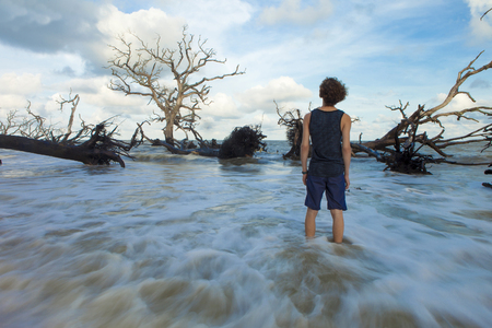 the flood tide: time exposure of young man standing in flowing water looking at dead flooded trees