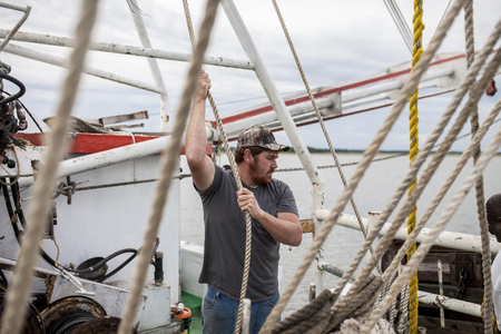 shrimp boat: Deckhand working on the deck of a fishing trawler