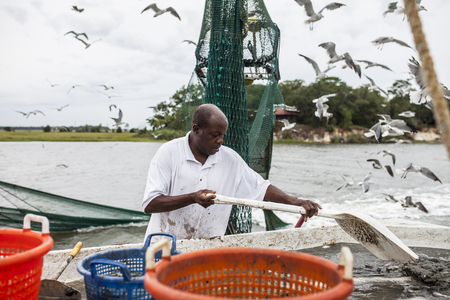 fisherman: african american commercial fisherman working on the deck of a fishing trawler Stock Photo