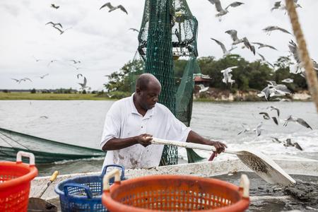 pecheur: african pêcheur commercial américain travaillant sur le pont d'un chalutier de pêche