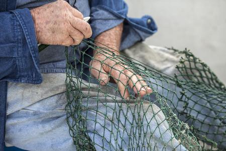 pecheur: Mains de pêcheur réparer les filets commerciaux Banque d'images