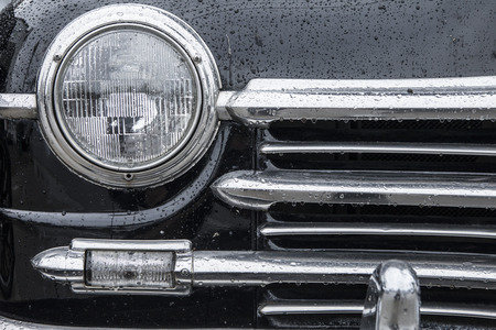 black car: closeup of classic car grill and headlamp with wet paint and chrome Stock Photo