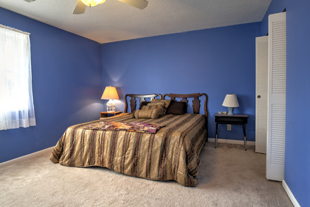 closet door: simple bedroom with queen size bed and blue walls