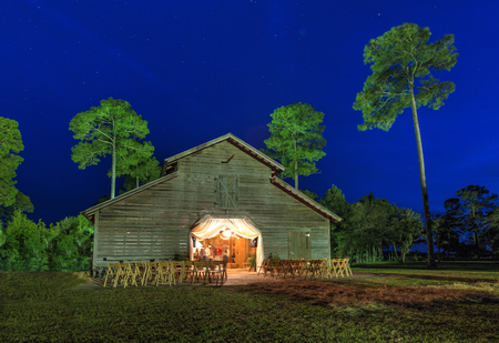 barn: Wedding reception in lit up barn at night