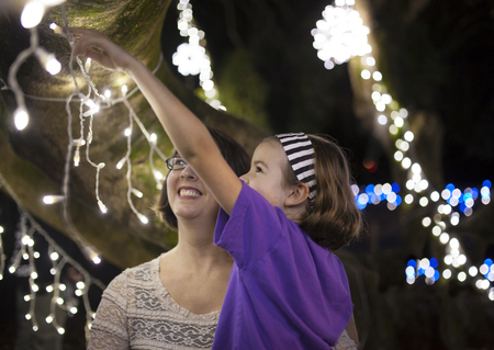 warm climate: mother and daughter enjoying holiday lights outside in warm climate