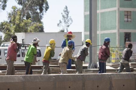 ADDIS ABABA, ETHIOPIA-OCTOBER 31, 2014: A foreign Chinese foreman directs local Ethiopian workmen on a railroad project in Addis Ababa, Ethiopia