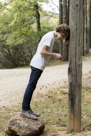 Teen texting while leaning his head against a pole