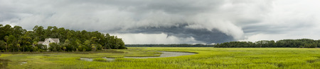 threatening: Threatening storm front moving over coastal home, wide panorama