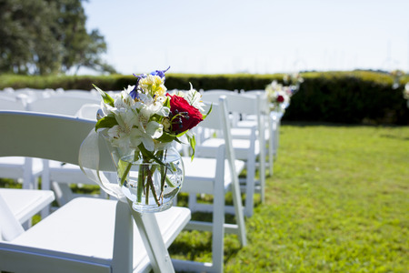 hanging flowers: Hanging flowers decorating chairs at wedding site Stock Photo