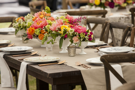 Dinner table with antique dishes and flowers for wedding reception Stok Fotoğraf - 67643991
