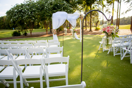 hanging flowers: chairs and arbor with hanging flowers for wedding, focus on flowers in jar
