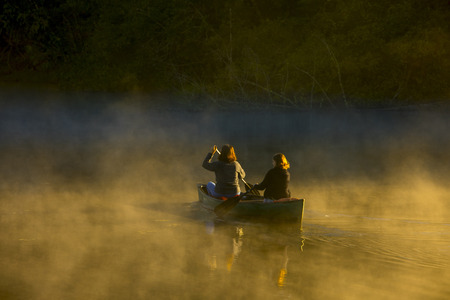Mother and daughter canoeing together in morning fog with sunlight