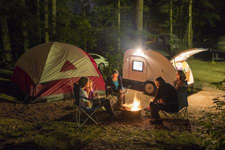 Familie van vijf kamperen bij nacht met kampvuur
