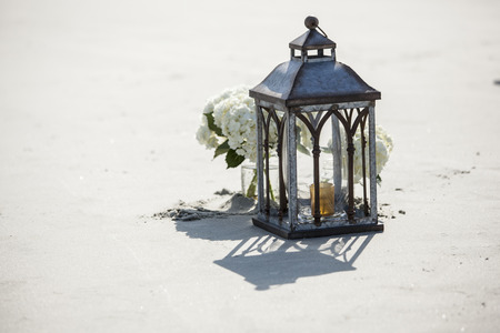 Hurricane lamp and mason jar with flowers for beach wedding