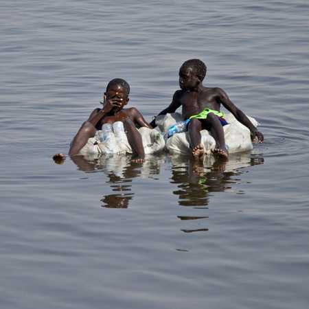 JUBA, SOUTH SUDAN-FEBRUARY 19, 2013: Unidentified kids float down the Nile river on sacks filled with empty water bottles. Editorial