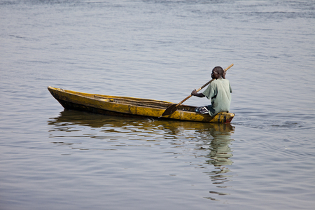 JUBA, SOUTH SUDAN-FEBRUARY 19 2013: unidentified man paddles traditionally made canoe on the White Nile through Juba, capital of South Sudan