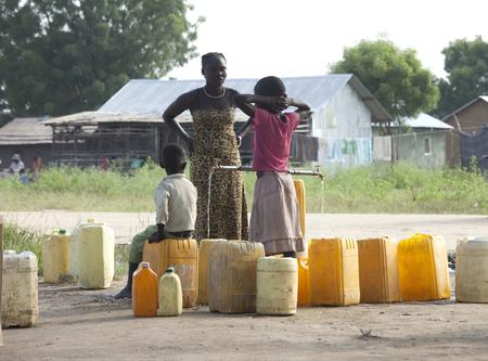 BOR, ZUIDEN SUDAN-OKTOBER 31, 2013: Niet-geïdentificeerde mensen vullen watercontainers op een vulpunt in Zuid-Soedan
