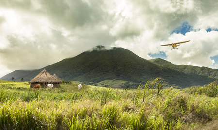 Small plane flying over huts in remote tropical location Stock Photo