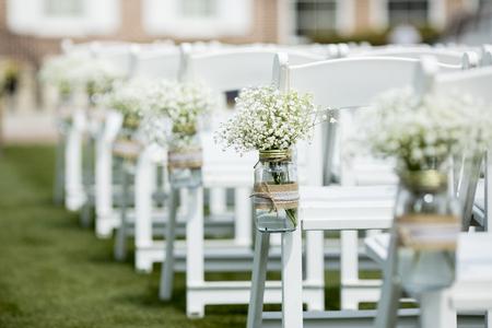 결혼식을 위해 의자에서 걸려 꽃과 항아리