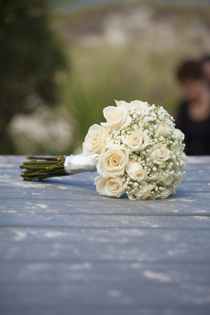 Bouquet of roses for wedding on sandy boardwalk for beach wedding