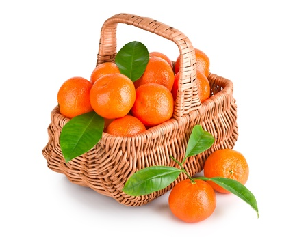 Ripe tangerines with leaves in basket isolated on white background  photo