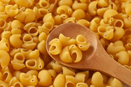 Italian pasta in shape of horns and wooden spoon photo