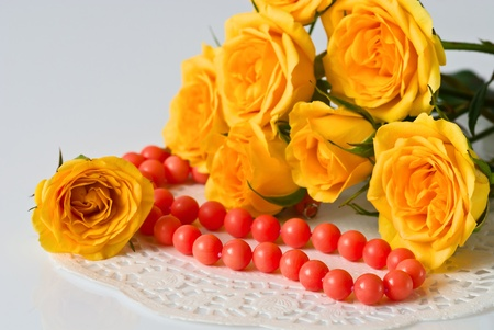 Yellow roses and coral beads Stock Photo
