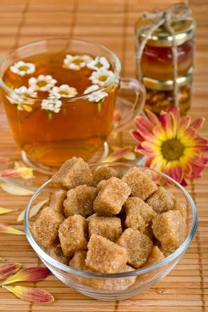 Cane brown sugar and herbal tea on bamboo napkin photo