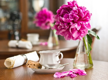 A cup of tea and biscuits and peony on wooden table Stock Photo