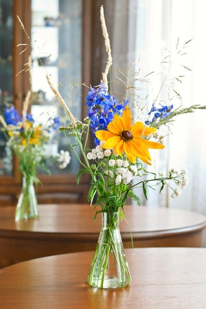 Bouquet of wild flowers on wooden table photo