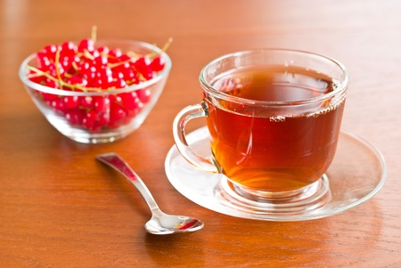 Glass tea cup and redcurrants in bowl on wooden table Stock Photo - 11796200