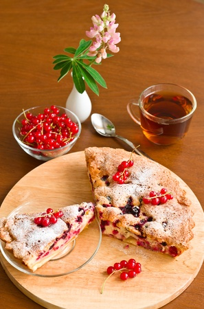 Cake, tea, red currant and lupine on wooden table