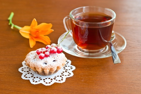 Cake, tea and flower on wooden background
