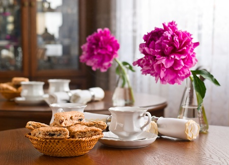 A cup of tea and biscuits and peony on wooden table photo