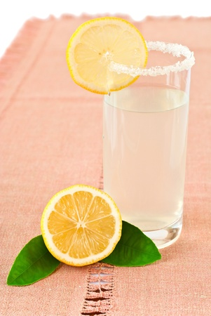 Glass of lemonade and lemon on a napkin photo