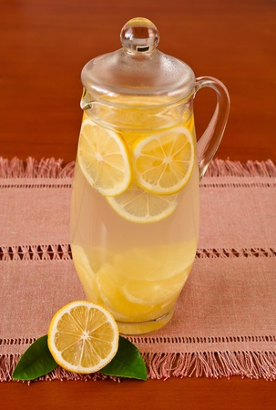 Glass pitcher of lemonade and lemon on napkin