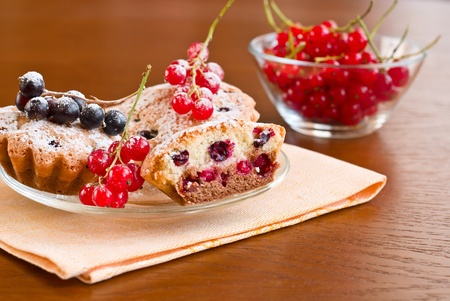 Muffins, red and black currants on a wooden background Stock Photo - 11852092
